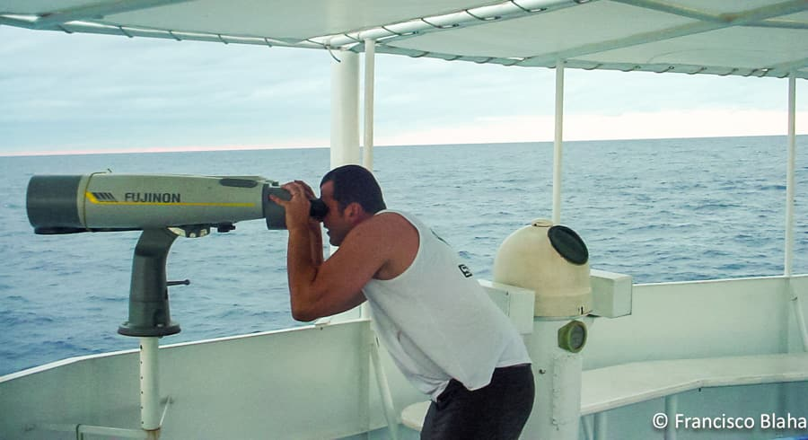 Francisco looking through telescope at work on board a purse seiner at Tokelau in 2002 (Photo: Francisco Blaha)