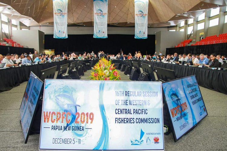 Inside the 16th Tuna Commission meeting in Port Moresby. Boards and banners displaying the words WCPFC 2019, and many people seated around the end of a room, with tables in a U formation. Photo: F. Tauafialfi.
