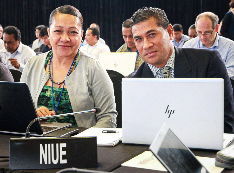 Niue's Associate Minister for Natural Resources, Hon. Esa Sharon-Mona Ainuu, left, at WCPFC16, sitting at a table in a meeting room, next to an unnamed man. Country label Niue in front of them, and they have laptop computers open in front of them, and a microphone.