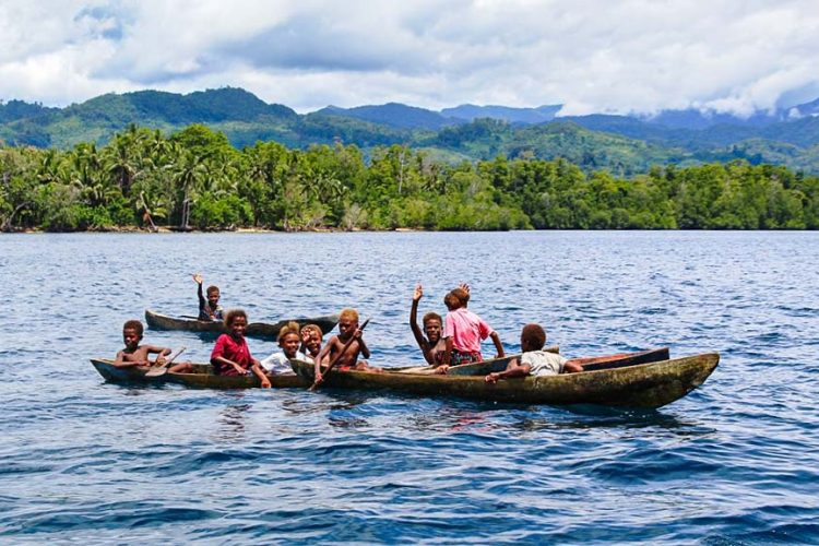Children in wooden dug-out canoes enjoying paddling near shore in Bina Harbour, Solomon Islands. Photo: Wilson B. Saeni.