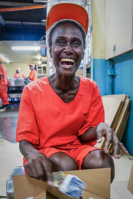 Laughing woman in orange cap and coverall clothing with paintbrush and box in factory Solomon Islands. Photo Francisco Blaha.