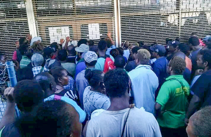 Densely packed group of Solomon Islanders outside building with security shutters down. Photo: Lachlan S. Eddie.