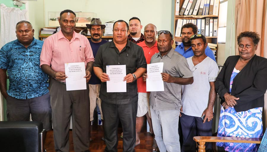 In Solomon Islands, nine men and one woman stand for photo in a room. Three of them hold in front of them copies of the same document. They are RIFF chair Lesley Assad Norris , the MP for Savo–Russells, the Hon. Dickson Mua, and Central Islands Province Premier Stanley Manetiva