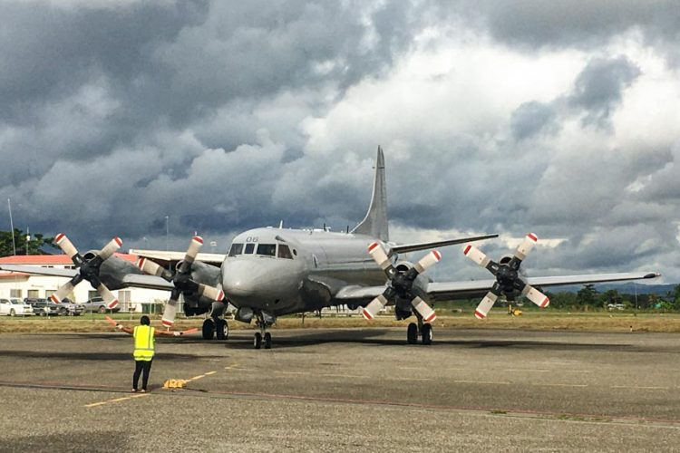 Royal New Zealand plane on runway at Honiara, Solomon Islands, for aerial surveillance of tuna fishing grounds, with man in front of plane with flags. Photo Vicki Stevens/FFA RFSC.