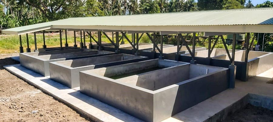 Newly built concrete pools, with roof, to be filled with water to hold tilapia, Aruligo hatchery, Guadalcanal
