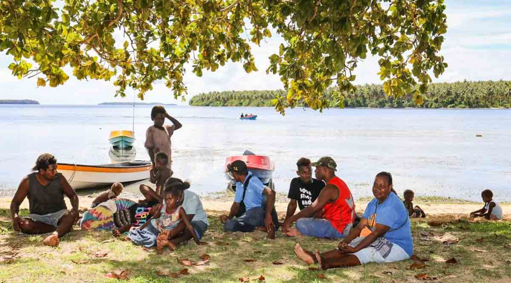 Group of women, men and children sitting under shade of tree on beach at Louna, Solomon Islands. Photo: Solomon Islands Government Communications Unit.