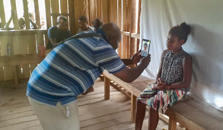 Man uses a tablet to take a photo of a young woman who is a tribal landowner at Bina Harbour, Malaita, Solomon Islands