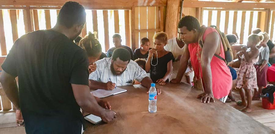 Man sits at table writing in book while other tribal landowner applicants look on, Bina Harbour beneficiary mapping, Solomon Islands