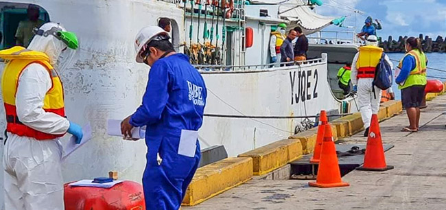 Among people on wharf and ship moored alongside in Apia, Samoa, are two wearing personal protective equipment to minimise the passing on of COVID-19.