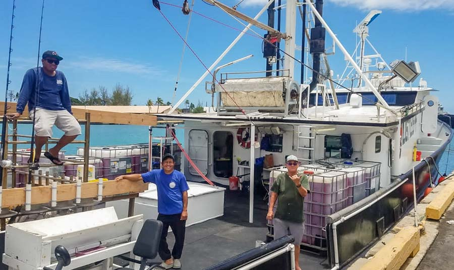 Three men on deck of research vessel Gutsy Lady 4 being prepared at Kewalo Basin, Honolulu, for the tuna tagging cruise in the central Pacific. Photo SPC.