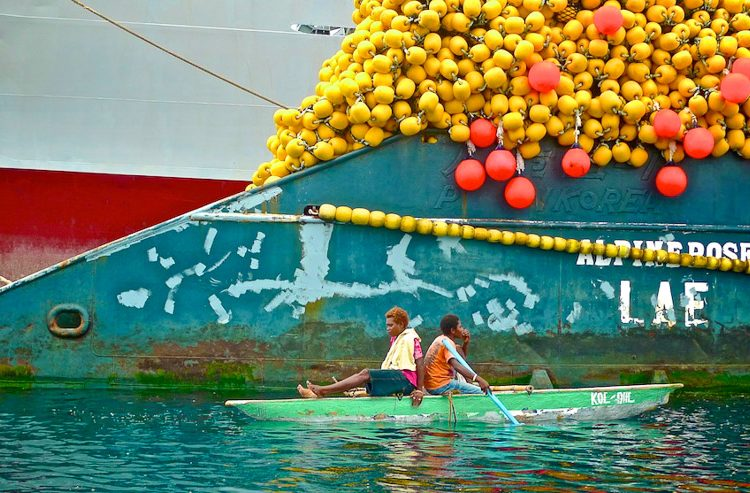 Two Papua New Guineans, among the owners of local fish resources, in front of a large fishing vessel at berth. Photo: Francisco Blaha.