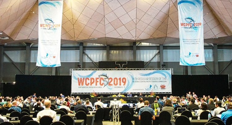 Large meeting hall hung with banners marked 'WVPFC 2019'. Four people sitting at a table on a dias, and scores of people sitting in seats around rows of long tables, at WCPFC16 in Port Moresby