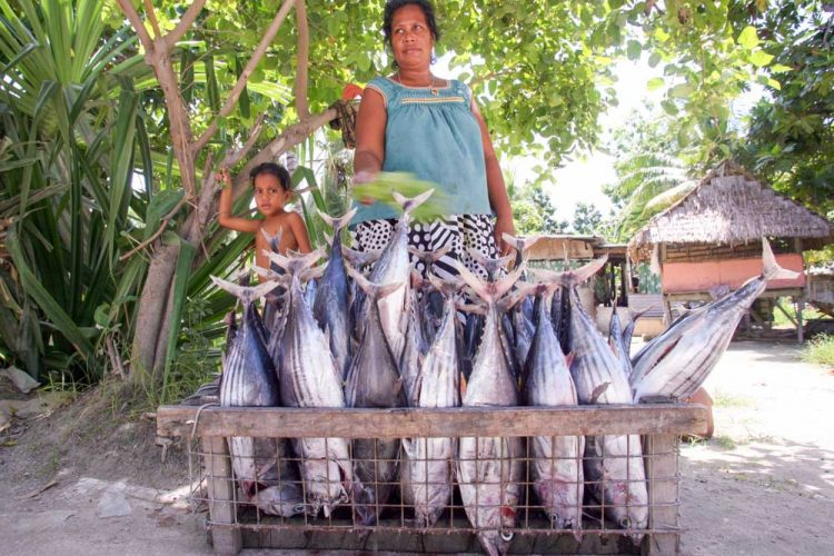 Woman standing behind crate of tuna for sale. Photo: Pacific Community.