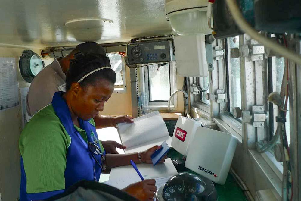 Woman checks documents on bridge of a ship. Photo: Francisco Blaha.