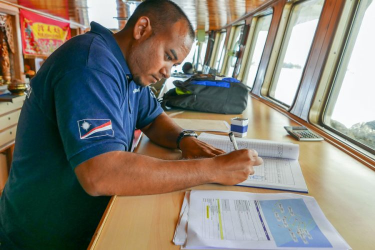 Fisheries officer checks documents on a fishing vessel that seeks access to the port of Majuro, Marshall Islands. Photo Francisco Blaha.