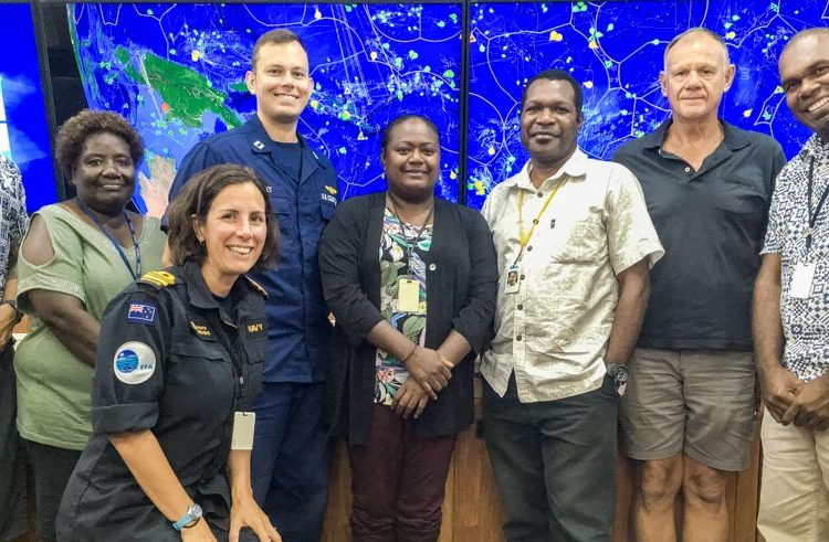 Three women and five men stand in front of monitoring screen at Regional Fisheries Surveillance Centre