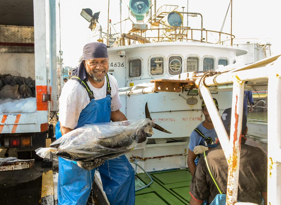Smiling man wearing bandana on head and large plastic apron holds whole bagged tuna on wharf. Fishing boat in background.