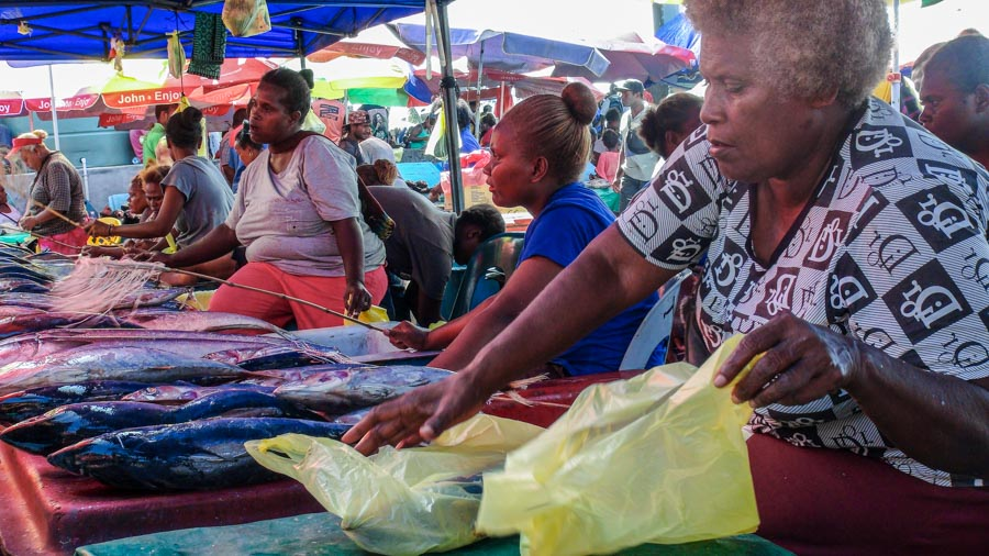 Women under awnings with tables laid with fresh tuna for sale at market