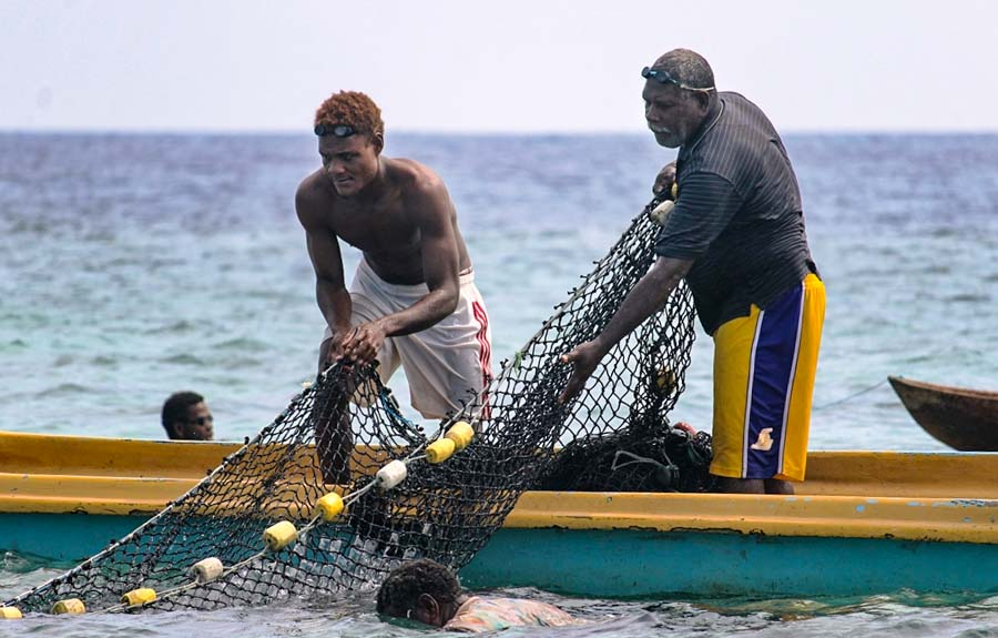 Two Fumamato'o men standing in open long boat haul in a net while fishing in the open-and-close area. Photo: WorldFish/Bira'au Wilson Saeni.