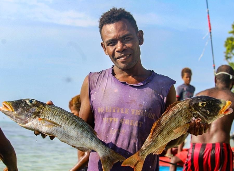Fumamato'o villager with his catch of two fish. Photo: WorldFish/Bira'au Wilson Saeni.
