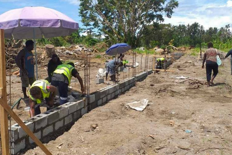 People building concrete block perimeter fence of Aruligo tilapia hatchery, Guadalcanal