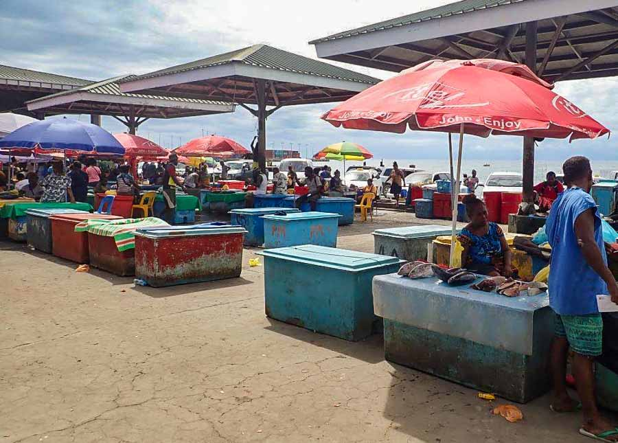 Fish vendors at Honiara. People work among ice-chests under the shade of shelters or umbrellas. Photo Sunday Isles.