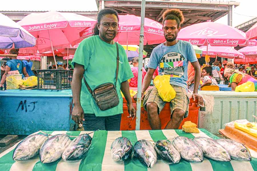 Sheroll Galo and John Kennedy were longtime salt fish vendors in Honiara. They are at a market, and positioned behind a table with 9 fish laid out on it, and in front of chiller boxes. Photo: George Maelagi.