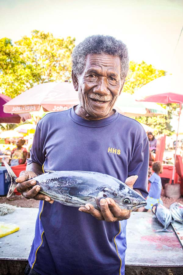 Chief of Solomon Islands village Vaivila, Robert Satu, is a longtime settler, fisher and fish vendor at the village. He stands at fish market with fish for sale in his hands. Photo: George Maelagi.