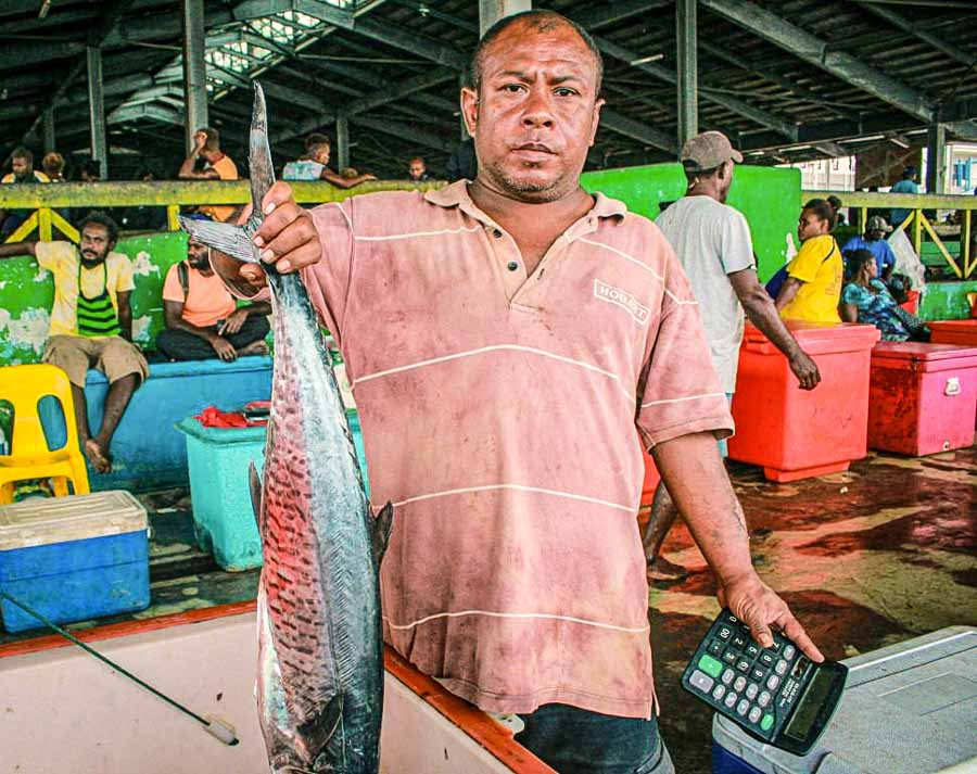 Sam, as he would want to be called, said the COVID-19 pandemic had had a huge impact on his fish-vending business at the Honiara Central Market. He stands at a market with a calculator in his left hand and a fish in his right. Photo: George Maelagi.