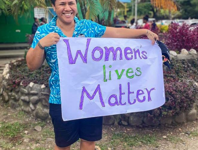 Joyce Samuela Ah-Leong, a fisheries management adviser with FFA, stands outside holding a home-made poster that says 'Women's lives matter'