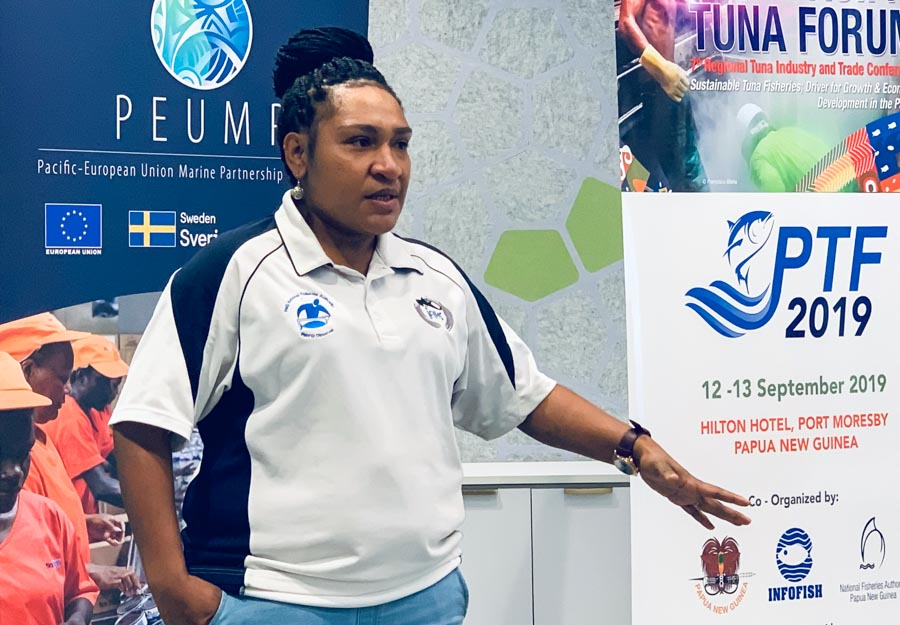 Rachael Luru, PIRFO observer and debriefer assessor for PNG Observer Programme, talking in front of posters