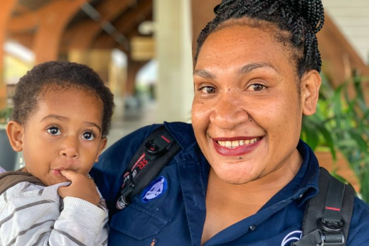 Head and shoulders photo of a young child and Rachael Luru, a PIRFO observer and debriefer assessor with the Papua New Guinea Observer Programme