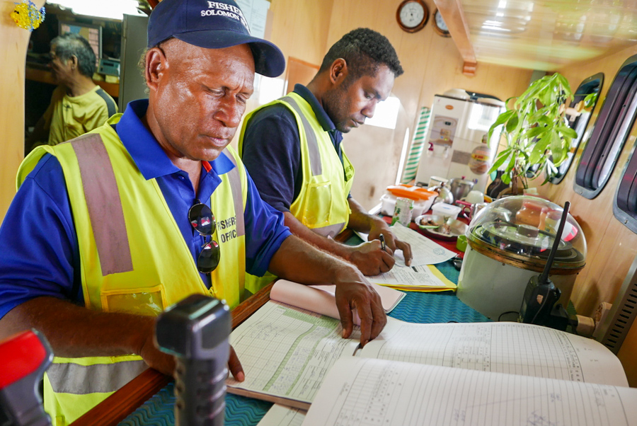 Two officers check log sheets of a Taiwanese longliner in Solomon Islands photo Francisco Blaha