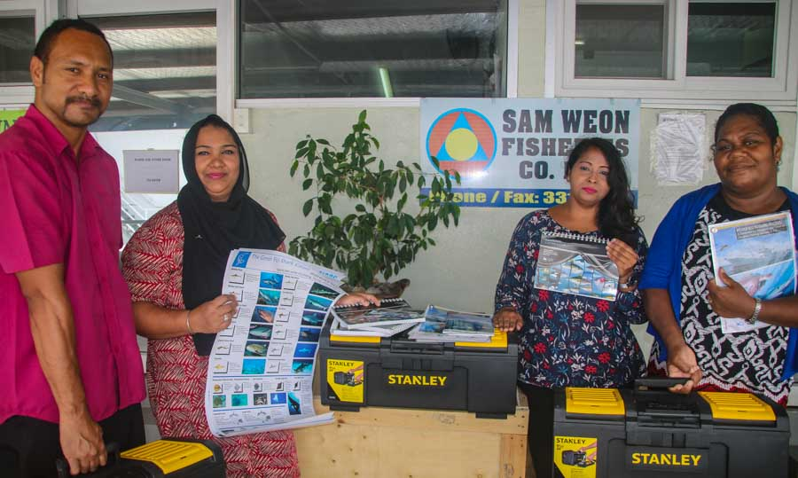 Sam Weon and the staff of Green Tuna Fisheries receive bycatch mitigation toolkits and awareness materials for fishing vessels. Photo: WWF-Pacific/Ravai Vafo'ou.