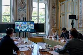 Officials seated around a desk looking at a Zoom meeting grid of faces on a monitor