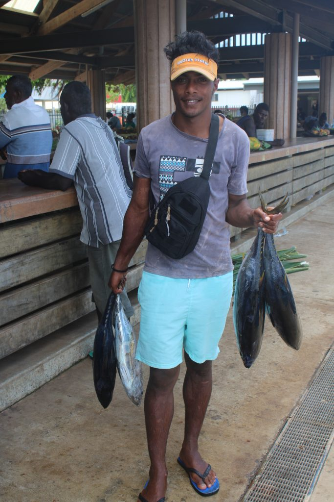 Young man holding 4 tuna standing near a market