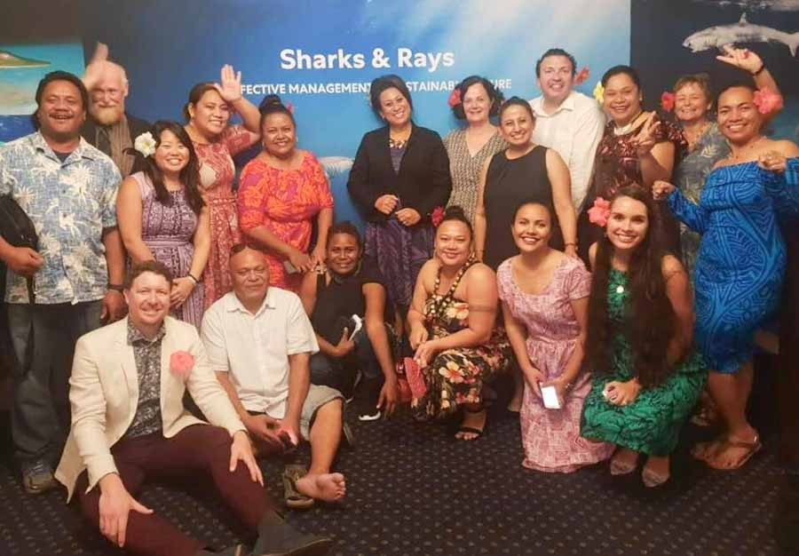 Group of 18 women and men, including some from Pacific Islands, standing before a shark poster