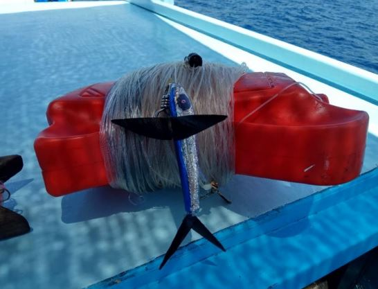 A lure attached to a hand line, rolled up on the deck of a boat