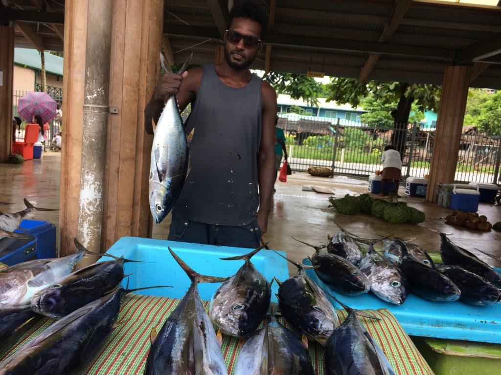 Man holding up a tuna for sale at a market near other tuna laid out